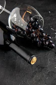 Widok na dolną połowę butelki wina przewrócony kieliszek do wina czarne winogrona