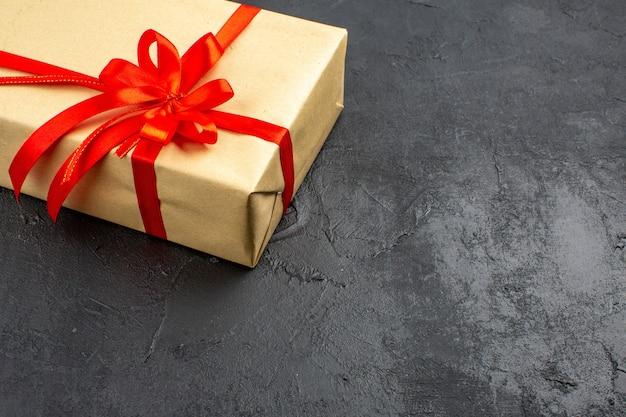 Widok na dolną połowę prezentu świątecznego w brązowym papierze związanym czerwoną wstążką na ciemnym tle