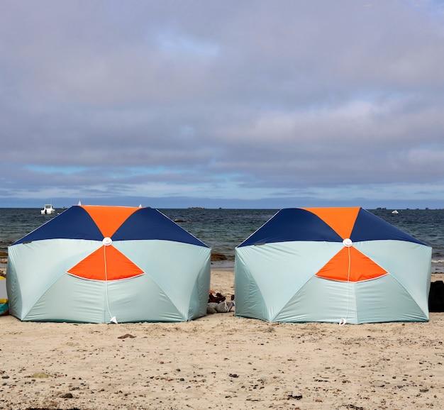 Widok na dwa parasole chroniące rodzinę przed słońcem