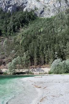 Widok na dziką plażę z białym górskim jeziorem żwirowym o turkusowym kolorze wody, klifów i lasu. pojęcie natury, góry, tor, podróż.