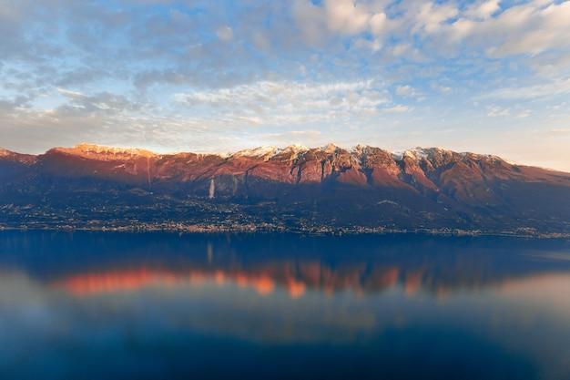 Widok na górę monte baldo ubarwiony promieniami zachodzącego słońca i odbity w spokojnych wodach jeziora grada
