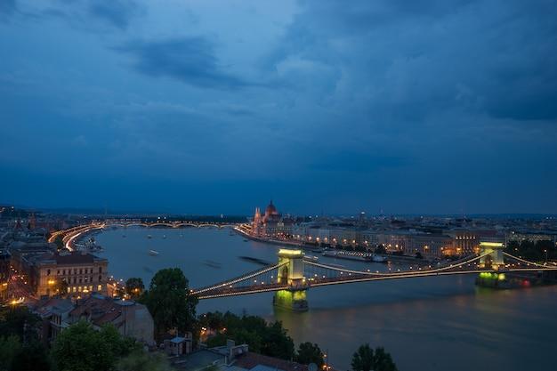Widok na gród dunaju w nocy z dużym mostem świetlnym w budapeszcie.