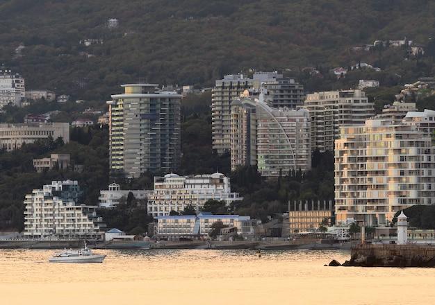 Widok na jałtę od strony morza latarnia morska hotele domy wakacyjne statek wieczorem