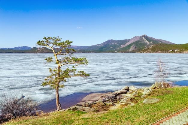 Widok na jezioro burabai pokryte jest lodem. jezioro znajduje się w parku narodowym burabay w republice kazachstanu. piękny górski krajobraz.