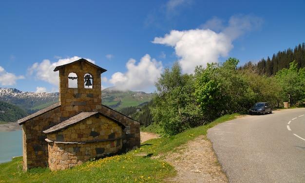 Widok na kamienną kaplicę nad jeziorem roselend we francji