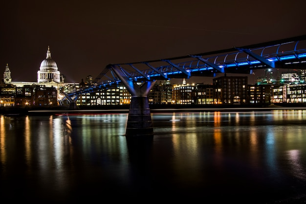 Widok na katedrę św. pawła i niebieskie światła na millenium bridge w nocy w londynie