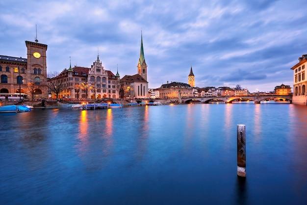 Widok na kościół fraumunster i kościół świętego piotra w nocy, zurych, szwajcaria