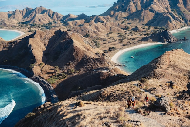 Widok na krajobraz ze szczytu wyspy padar w labuan bajo z turystami idącymi w dół wzgórza