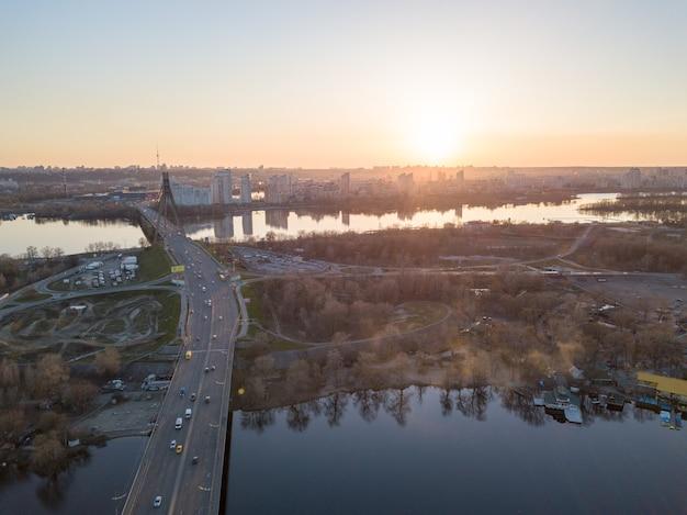 Widok na lewą część miasta kijowa z mostu północnego nad dnieprem oraz widok na centrum handlowe skaimol w okolicy obolon na pięknym zachodzie słońca. zdjęcie z drona