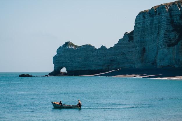 Widok na łódź z dwiema osobami poruszającą się obok etretat