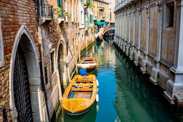 Widok na łodzie w wąskim kanale w wenecji, włochy