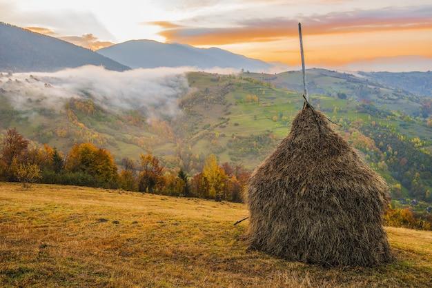 Widok na malowniczy krajobraz z jasnym kolorowym niebem nad mglistymi górami. majestatyczny wschód słońca w dolinie mglistego poranka ze stogiem siana na wzgórzu trawiastym. pojęcie natury.