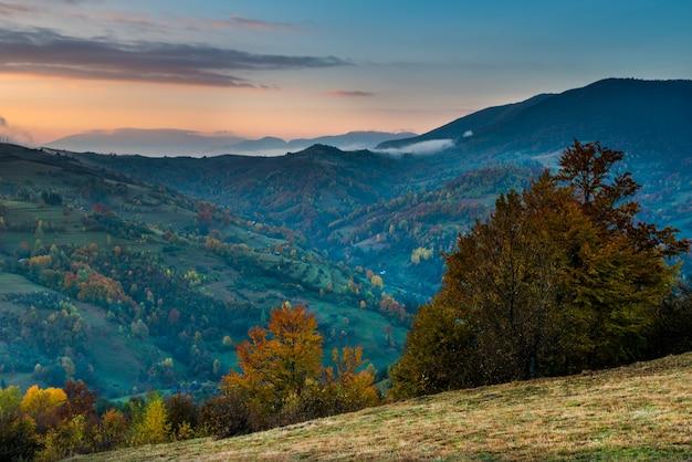 Widok na malowniczy krajobraz z jasnym kolorowym niebem nad zamglonymi górami. majestatyczny wschód słońca w dolinie mglistego poranka ze stogiem siana na wzgórzu trawiastym. pojęcie natury.