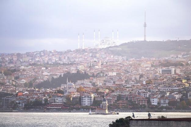 Widok na meczet camlica położony na wzgórzu z budynkami mieszkalnymi, cieśniną bosfor i wieżą leandera, stambuł, turcja