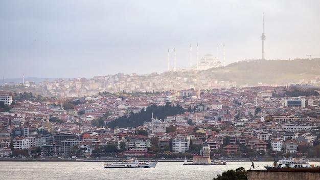 Widok na meczet camlica położony na wzgórzu z budynkami mieszkalnymi, cieśniną bosfor, pływającym statkiem i wieżą leandera, stambuł, turcja