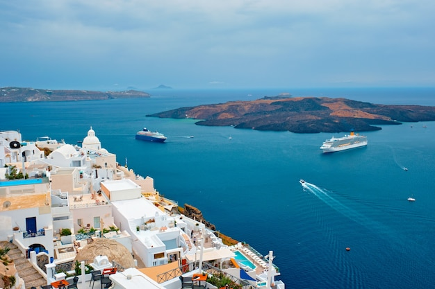 Widok na miasto fira na wyspie santorini ze statkami wycieczkowymi na morzu