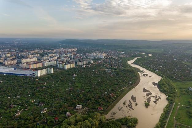 Widok na miasto iwano-frankiwsk z dzielnicą mieszkaniową i domami na przedmieściach z rzeką pośrodku.