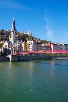 Widok na miasto lyon z czerwoną kładką na rzece saone i kościół