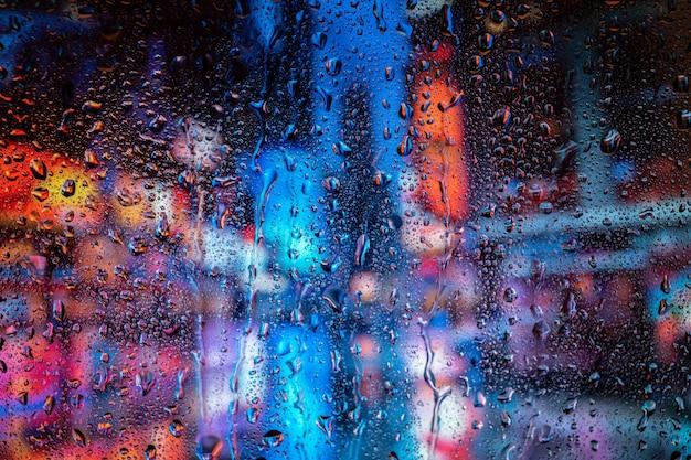 Widok na miasto przez okno w deszczową noc z bokeh światła drogowego.