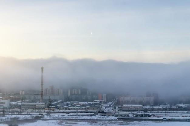Widok na miasto spowite porannym smogiem, na niebie księżyc.