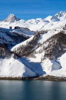 Widok na miejscowość tignes w zimie z jeziorem we francji.