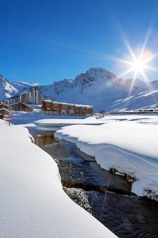 Widok na miejscowość tignes ze słońcem i potokiem we francji.