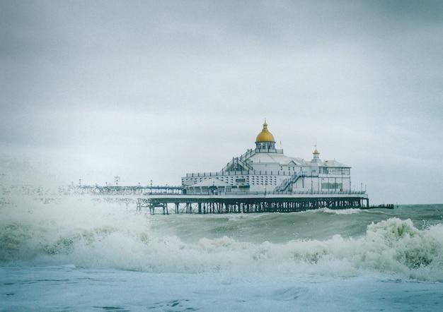 Widok na molo w eastbourne w anglii z silnymi falami na oceanie