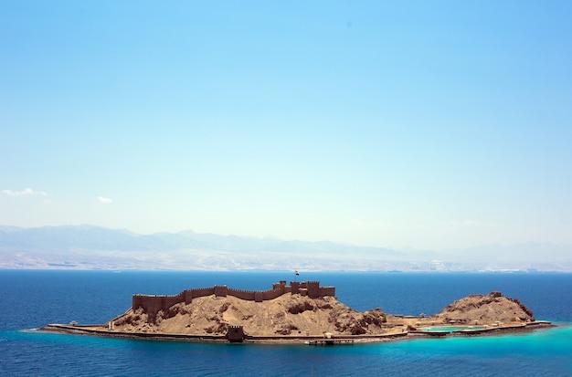 Widok na morze czerwone z wyspą salah al din i zamkiem w taba, egipt