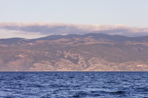 Widok na morze i góry na zachód lub wschód słońca. wielkość i spokój krajobrazu