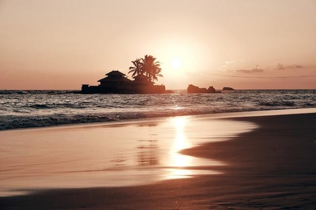 Widok na morze wieczorem zachód słońca i dom na wyspie