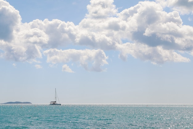 Widok na morze z górami w oddali i łodziami?