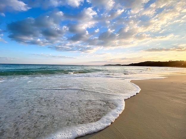 Widok na morze z tropikalnej plaży ze słonecznym niebem wieczorem. letnia plaża z chmurami na horyzoncie.