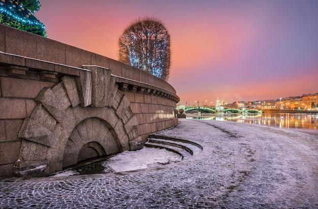 Widok na most birzhevoy ze strelki wyspy wasiljewskiej w sankt petersburgu w różowy zimowy poranek