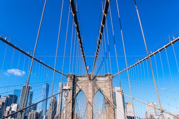 Widok na most brookliński z ukośnymi fiszbinami i pionowymi linkami do pończoch. w centrum zdjęcia powiewająca na wietrze flaga amerykańska.