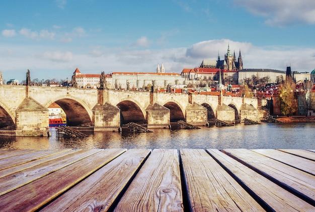 Widok na most karola, który przecina rzekę wełtawę i drewniane molo na pierwszym planie