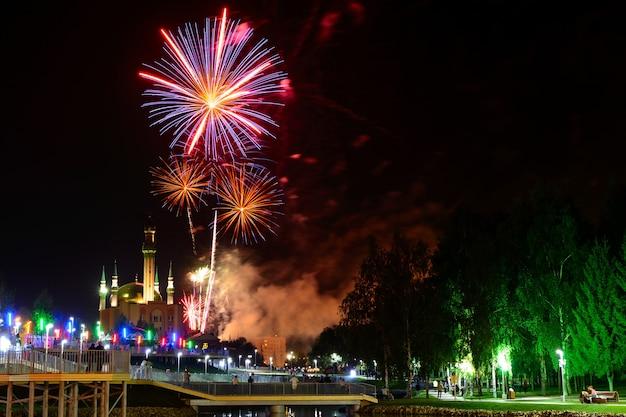 Widok na nocne niebo i piękne fajerwerki eksplodujące w mieście