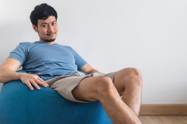 Widok na nogi mężczyzny na białym łóżku z telewizorem i rośliną. pojęcie relaksu.