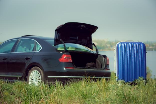 Widok na nowoczesny czarny samochód i niebieską walizkę od strony rzeki w słoneczny dzień.