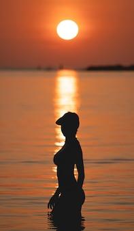 Widok na ocean o zachodzie słońca. słońce nad morzem na pomarańczowym niebie. kobieta stojąca na plaży.