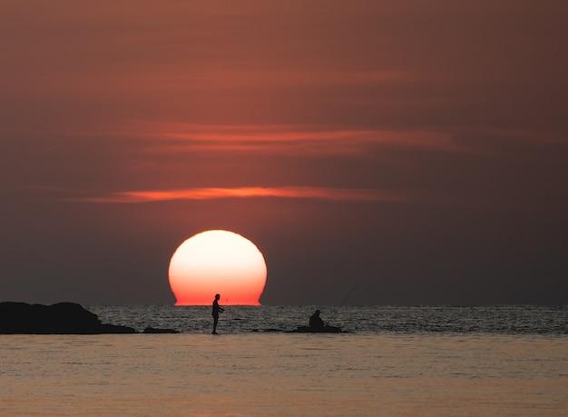 Widok na ocean o zachodzie słońca. słońce nad morzem na pomarańczowym niebie. rybak z wędką na skale.