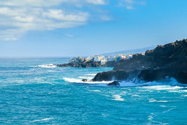 Widok na oceanu brzeg i kolorowi budynki na skale w punta brava, puerto de la cruz, tenerife, wyspy kanaryjska, hiszpania