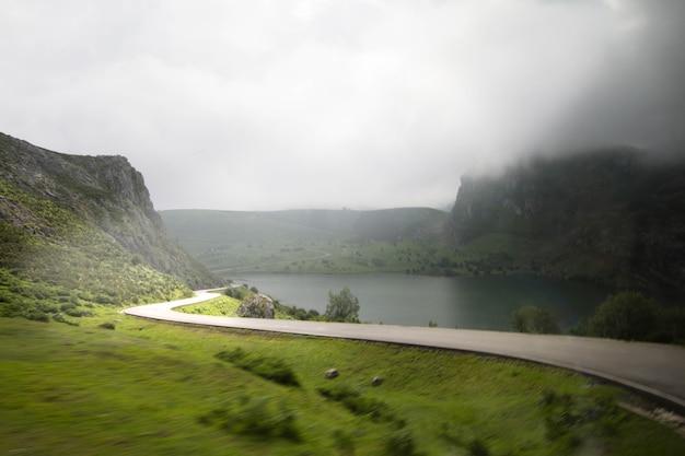 Widok na odległą autostradę z samochodu jedź w górzystym otoczeniu z jeziorami