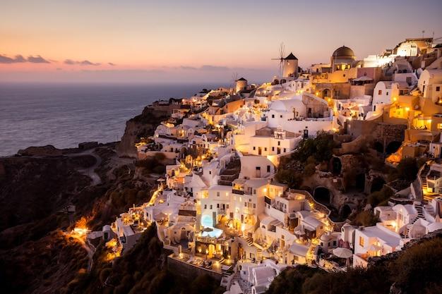Widok na oia o zachodzie słońca, wyspa santorini, grecja