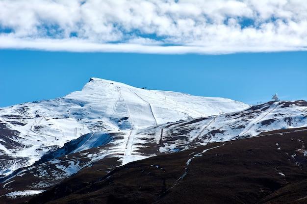 Widok na ośrodek narciarski sierra nevada w granadzie w hiszpanii, w niskim sezonie śnieżnym. korzystanie ze sztucznych armatek śnieżnych