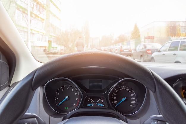 Widok na oświetloną w słońcu kierownicę z prędkościomierzem i obrotomierzem