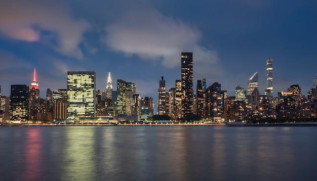 Widok na panoramę manhattanu, nowy jork, usa, w nocy, z okolic dumbo. fotografia z długim czasem naświetlania, z odbiciami w wodzie o jedwabnej fakturze d