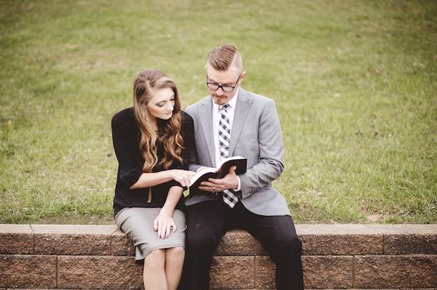 Widok na parę czytającą książkę i omawiającą ją, siedząc w ogrodzie