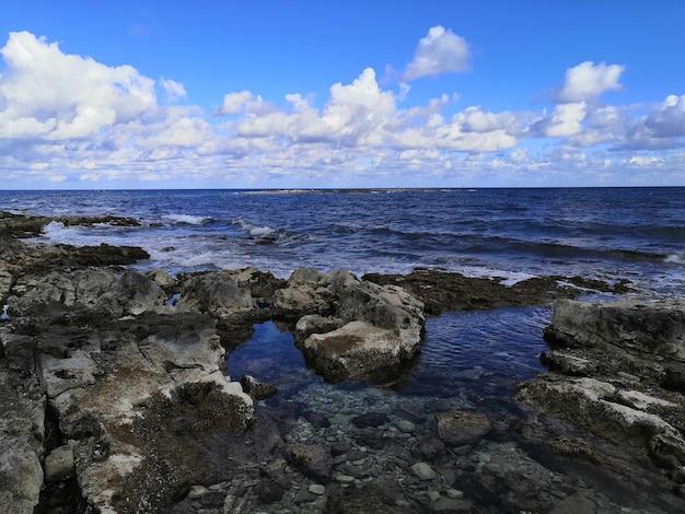 Widok na piękną spokojną plażę ze skałami na malcie uchwycony w słoneczny dzień