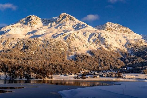 Widok na piękne góry śniegu za jeziorem silvaplana i jego wioską w szwajcarii podczas zimowego zachodu słońca