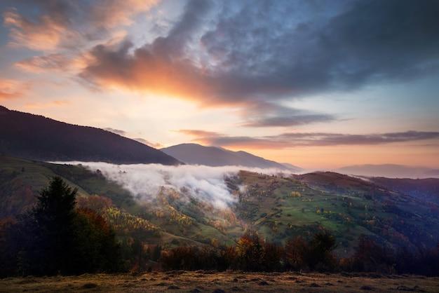 Widok na piękne pochmurne niebo nad łąką na zboczu wzgórza. majestatyczny krajobraz gór z dymem i dramatyczne jasne niebo na tle. pojęcie natury i świtu.
